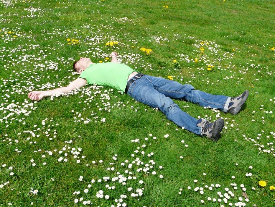 homme allongé dans l'herbe qui ressent les bienfaits du jardin