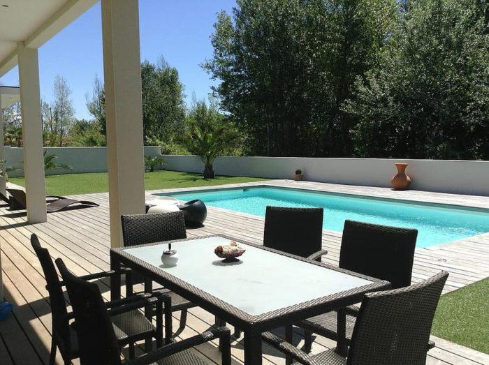 aménagement de jardin autour de la piscine avec espace repas et murs